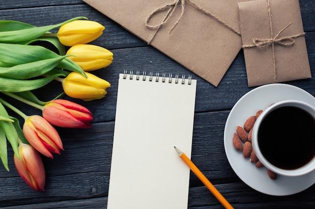 Blocnote met potlood naast de tulpen, de koffie, en de enveloppen. Premium Foto