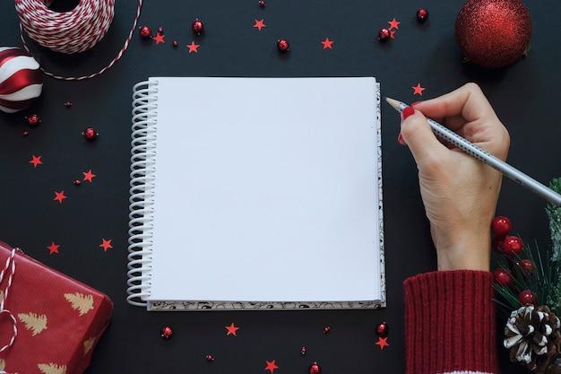 Blocnote op zwarte feestelijke achtergrond met rode decoratie. kerst concept Premium Foto