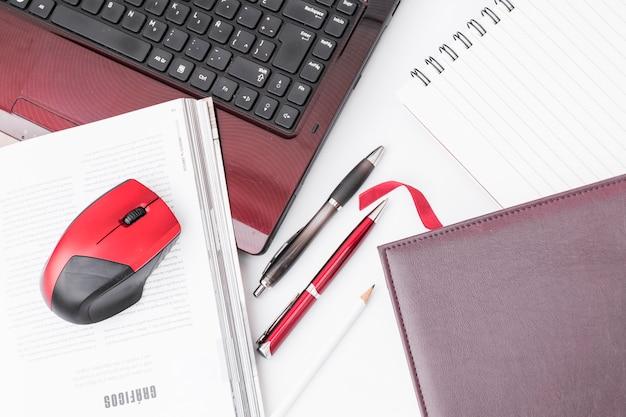 Blocnotes en pennen in de buurt van laptop en muis Gratis Foto