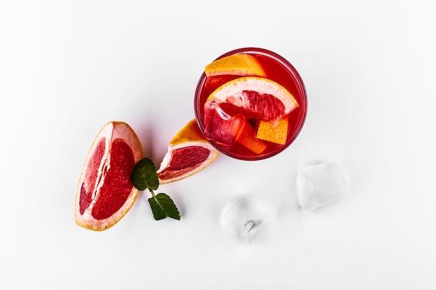 Bloed oranje gin-tonic cocktail geserveerd met plakjes sinaasappel en ijs in een glas Gratis Foto