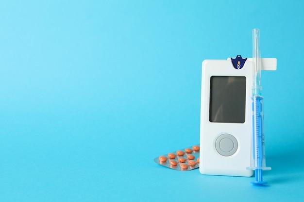 Bloedglucosemeter, spuit en pillen op blauwe achtergrond Premium Foto