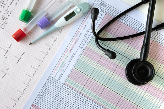 Bloedonderzoek, een digitale thermometer en een stethoscoop bovenop een tafel Premium Foto