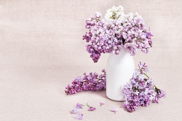 Bloeiende lilac bloemen in witte vaas op plattelander Premium Foto