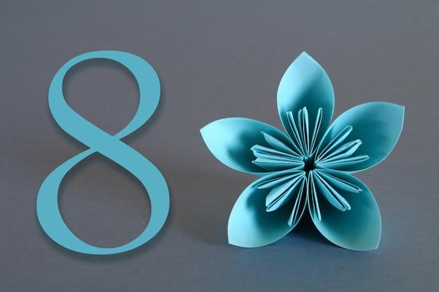 Bloem van origami met het nummer acht op een grijze achtergrond. 8 maart, internationale vrouwendag. Premium Foto