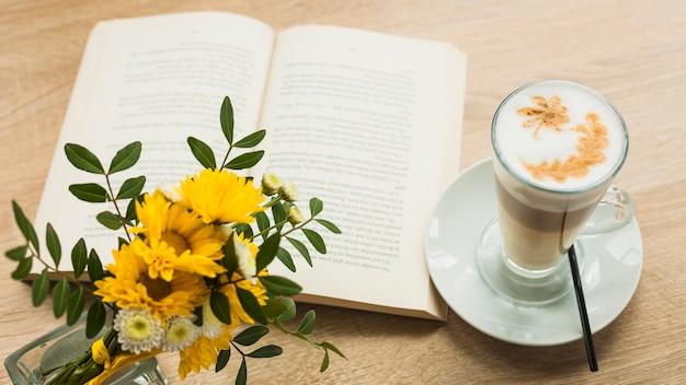 Bloem vas en latte koffiekop met open boek op houten gestructureerde oppervlak Gratis Foto