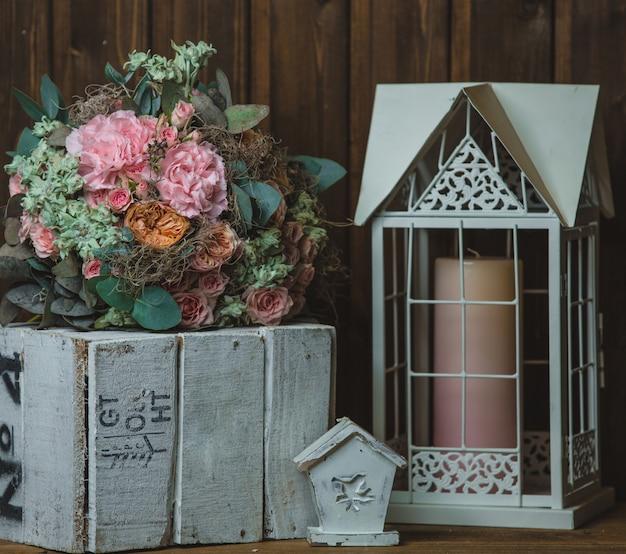 Bloemboeket, kaars in de kooi en rustieke houten kist Gratis Foto