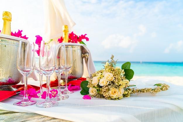 Bloemen boeket en glas en champagne in huwelijksboog Premium Foto
