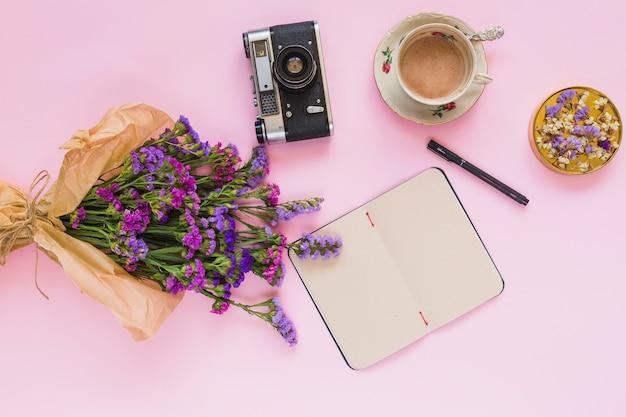 Bloemen boeket; vintage camera; dagboek; pen; koffiekopje en coaster op roze achtergrond Gratis Foto