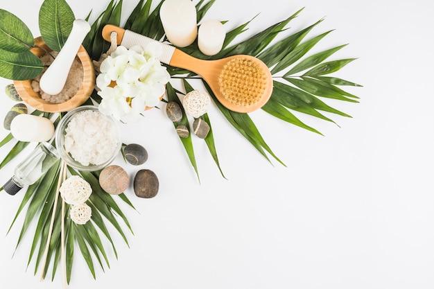 Bloemen; borstel; spa stenen; zout; kaarsen; oliefles op wit oppervlak Gratis Foto