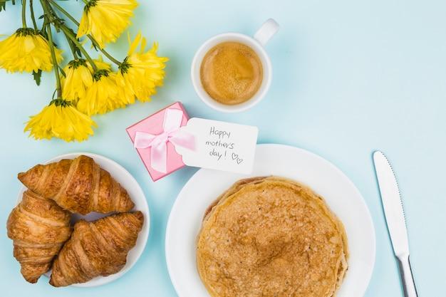 Bloemen dichtbij huidig met markering en platen met pannekoeken en croissants Gratis Foto