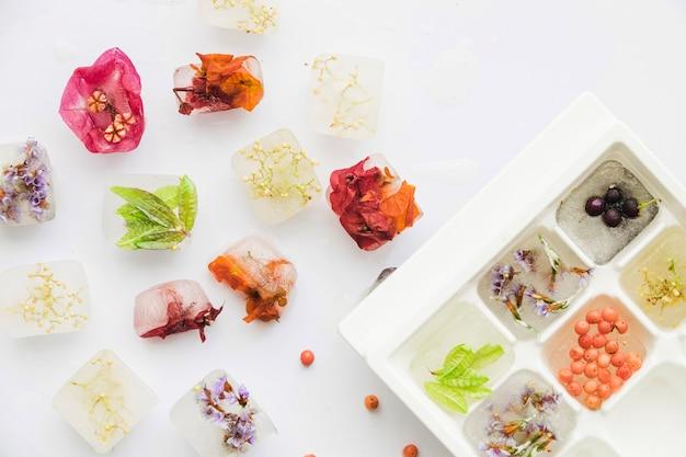 Bloemen en bessen in ijsblokken en dienblad Gratis Foto