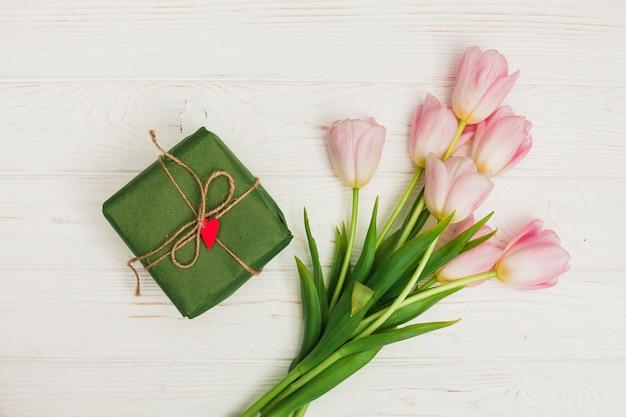 Bloemen en geschenkdoos op witte houten tafel Gratis Foto