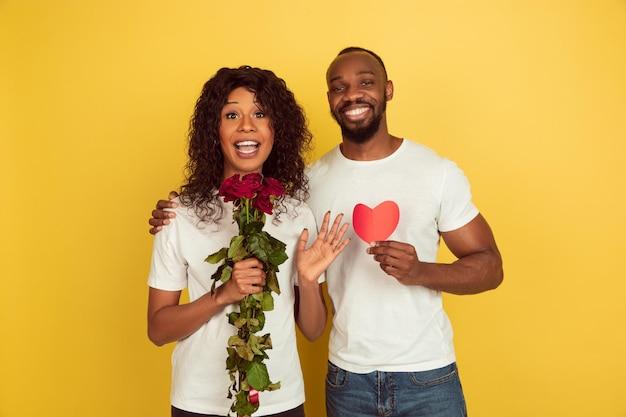 Bloemen en hart. valentijnsdagviering, gelukkig afrikaans-amerikaans paar dat op gele studioachtergrond wordt geïsoleerd. Gratis Foto