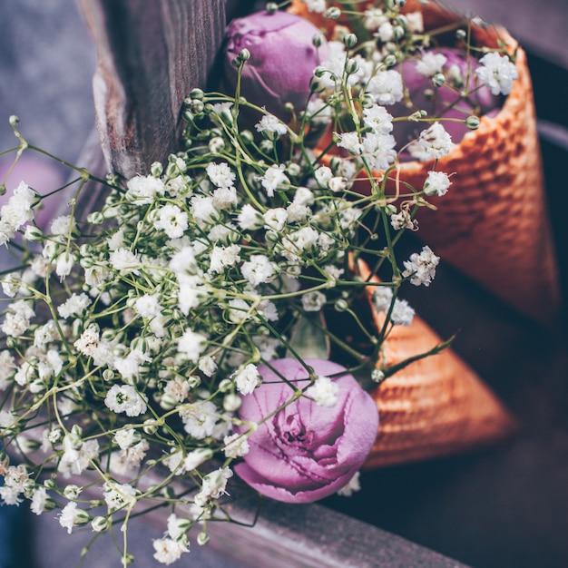 Bloemen en roze roos in wafel kegel in houten kist Premium Foto