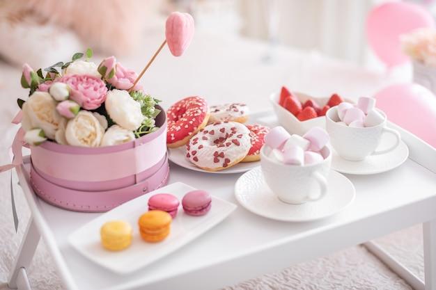 Bloemen en snoep op witte tafel en ballonnen op het witte bed. cadeau voor moederdag Premium Foto