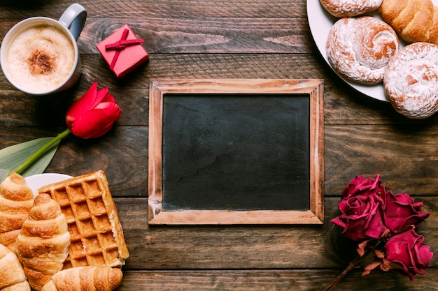 Bloemen, fotolijst, bakkerij op borden, geschenkdoos en beker drinken Gratis Foto