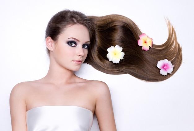 Bloemen in het mooie lange rechte glanzende haar van meisje op wit Gratis Foto