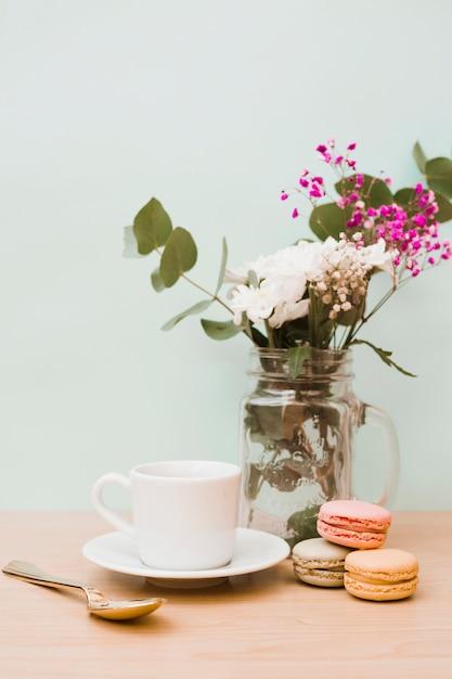 Bloemen in pot met beker; lepel en bitterkoekjes op houten bureau tegen de muur Gratis Foto