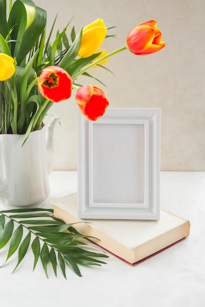 Bloemen in vaas en fotolijst op lijst dichtbij muur worden geplaatst die Gratis Foto