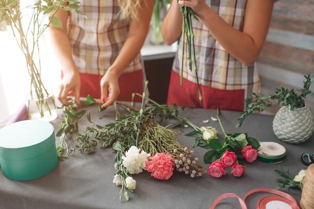 Bloemen levering bovenaanzicht. bloemisten die orde creëren, rozenboeket maken in bloemenwinkel. twee vrouwelijke bloemisten doen boeketten. een vrouw verzamelt rozen voor een stel, een ander meisje werkt ook. Premium Foto