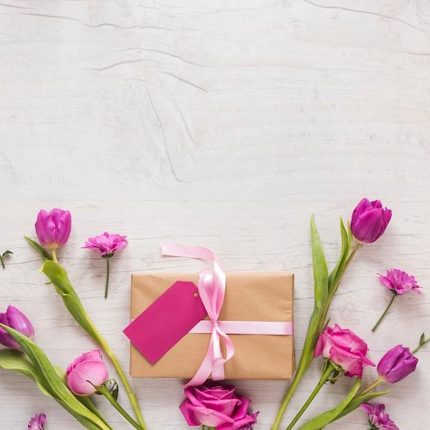 Bloemen met geschenkdoos op houten tafel Gratis Foto