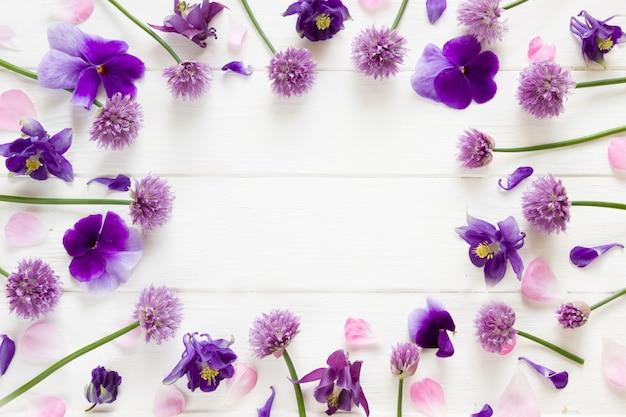 Bloemen plat ontwerp, paarse en roze bloemen op wit houten bord, floral frame in plat lag stijl met plaats voor uw tekst Premium Foto