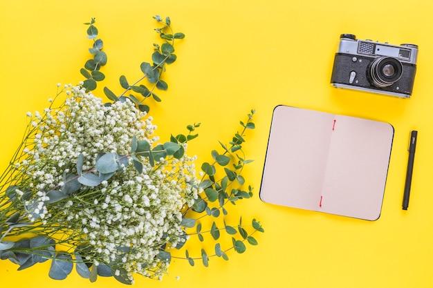 Bloemen voor baby's; dagboek; pen en vintage camera op gele achtergrond Gratis Foto