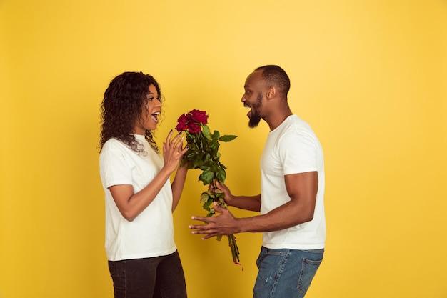 Bloemen voor een glimlach. valentijnsdagviering, gelukkig afrikaans-amerikaans paar dat op gele studioachtergrond wordt geïsoleerd. Gratis Foto