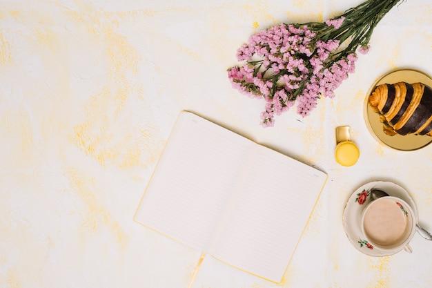 Bloemenboeket met notitieboekje, koffie en croissant op lijst Gratis Foto