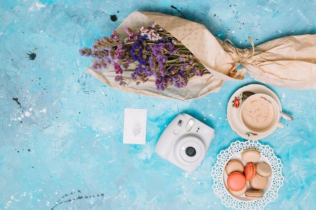 Bloemenboeket met onmiddellijke camera, koffiekop en koekjes Gratis Foto