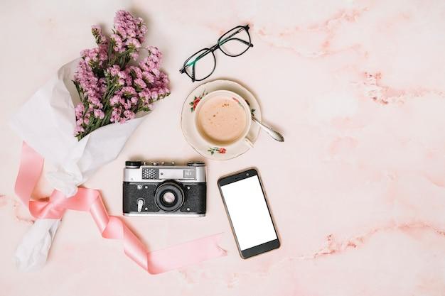 Bloemenboeket met smartphone en koffiekop Gratis Foto