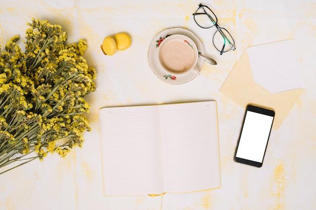 Bloemenboeket met smartphone, koffie en notitieboekje op lijst Gratis Foto