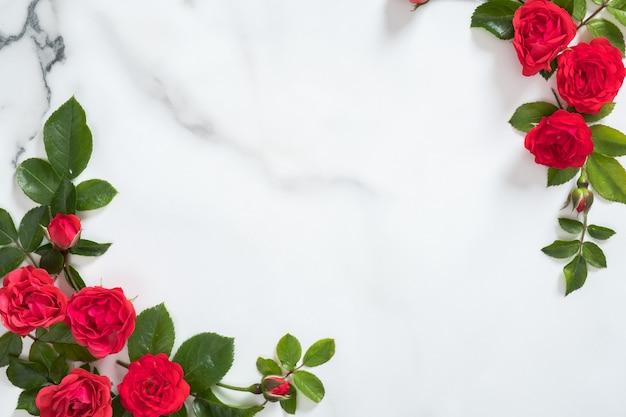Bloemenkader met rozenknoppen en groene bladeren op marmeren achtergrond Premium Foto