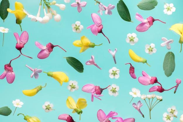 Bloemenpatroon. bloemen patroon textuur. bloemenpatroon gemaakt van roze en witte bloemen op aqua achtergrond. plat lag, bovenaanzicht. Premium Foto