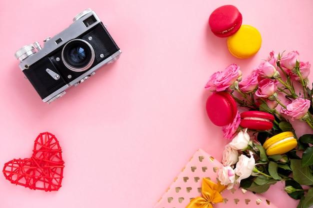 Bloemensamenstelling met een kroon van roze rozen en retro camera op roze achtergrond. valentijnsdag achtergrond. plat lag, bovenaanzicht. Premium Foto