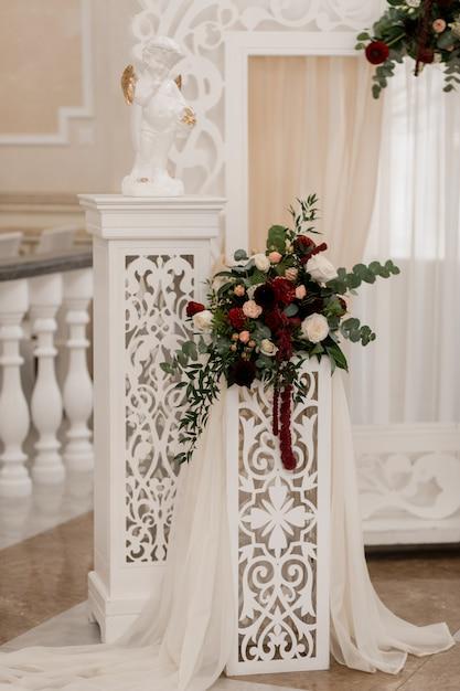 Bloemensamenstelling op de witte boog in de huwelijksceremoniezaal Gratis Foto