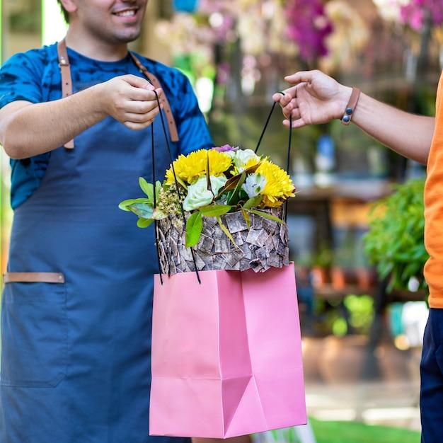 Bloemenwinkelmedewerker, bloemist die een bloemenboetiek aan de klant geeft Premium Foto