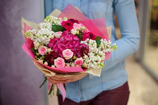 Bloemist die een mooi wit en roze boeket bloemen houdt Premium Foto
