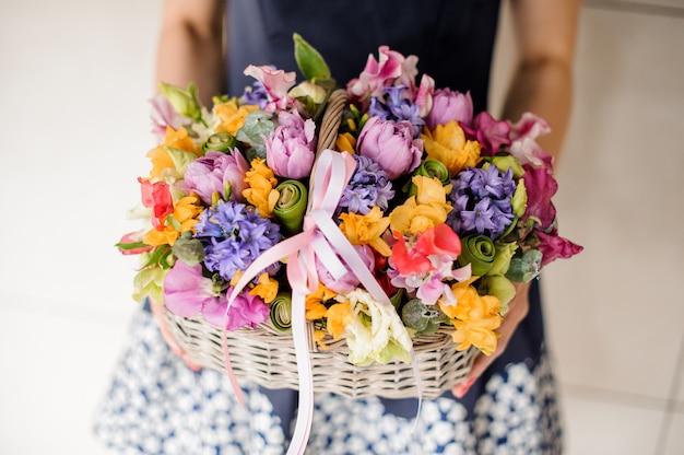 Bloemist die mooie rieten mand met bloemen houdt Premium Foto