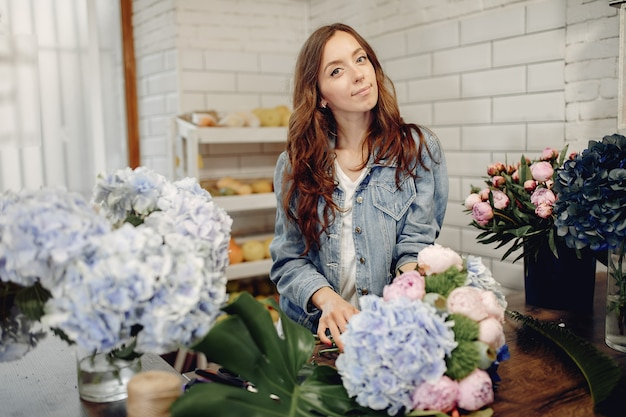 Bloemist in een bloemenwinkel die een boeket maakt Gratis Foto