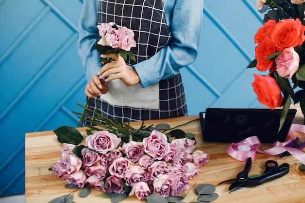 Bloemist maakt een mooi boeket in een studio Gratis Foto