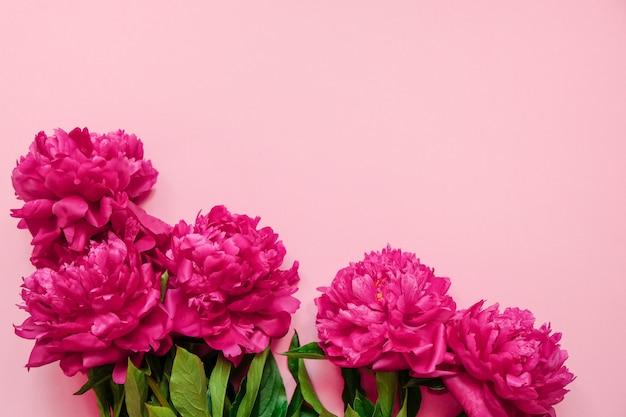 Bloemkader met verse takken van roze pioen op pastelkleur roze achtergrond met exemplaarruimte Premium Foto