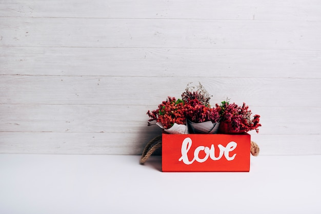 Bloemkegels in de liefdedoos op wit bureau tegen houten achtergrond Gratis Foto