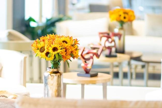 Bloemstuk van zonnebloemen die de woonkamer van het huis versieren Premium Foto