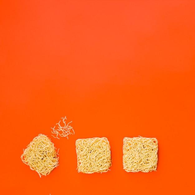 Blokken van onmiddellijke noedels gerangschikt op fel oranje oppervlak Gratis Foto