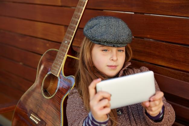 Blond jong geitjemeisje die selfie gitaar en de winterbaret nemen Premium Foto