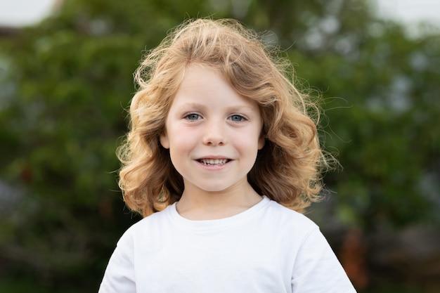 Blond kind met lang haar buitenshuis Premium Foto