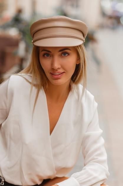 Blond lachende europese vrouw in trendy autun glb poseren buiten Gratis Foto