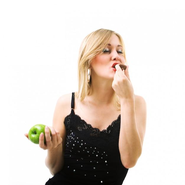 Blond meisje dat chocolade eet in plaats van appel Premium Foto