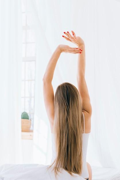 Blond meisje die zich uitstrekt op het bed Gratis Foto